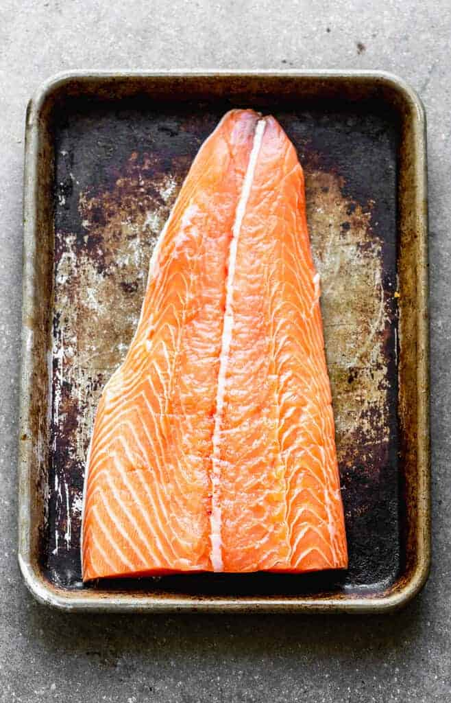 A dark baking sheet with a filet of raw, fresh salmon on it.