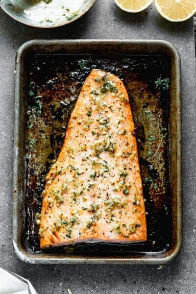 A filet of salmon baked on a baking sheet, topped with a lemon garlic sauce.