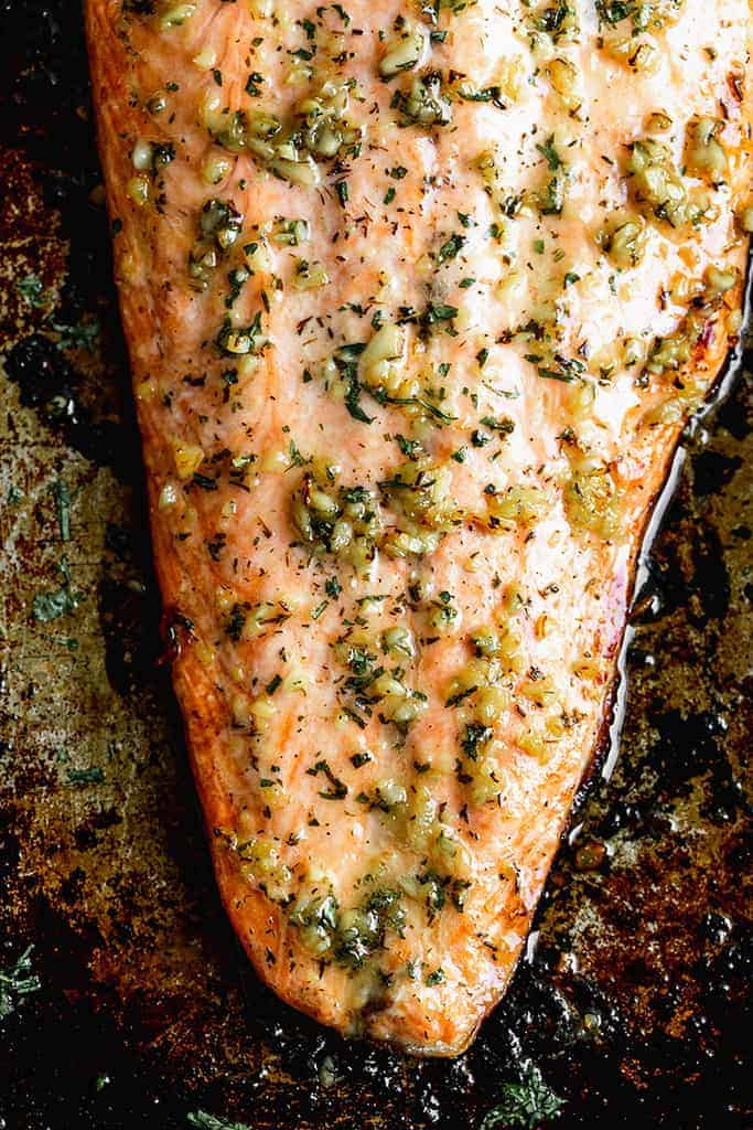 Close up photo of baked salmon with garlic butter topping.