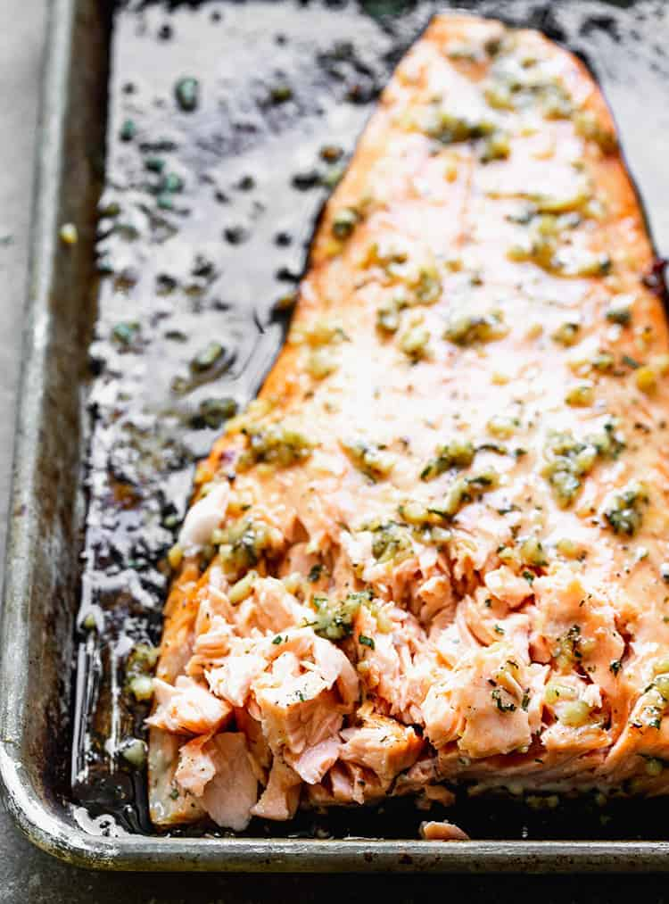 A baked salmon filet with the front edge flaked from a fork to test for doneness.