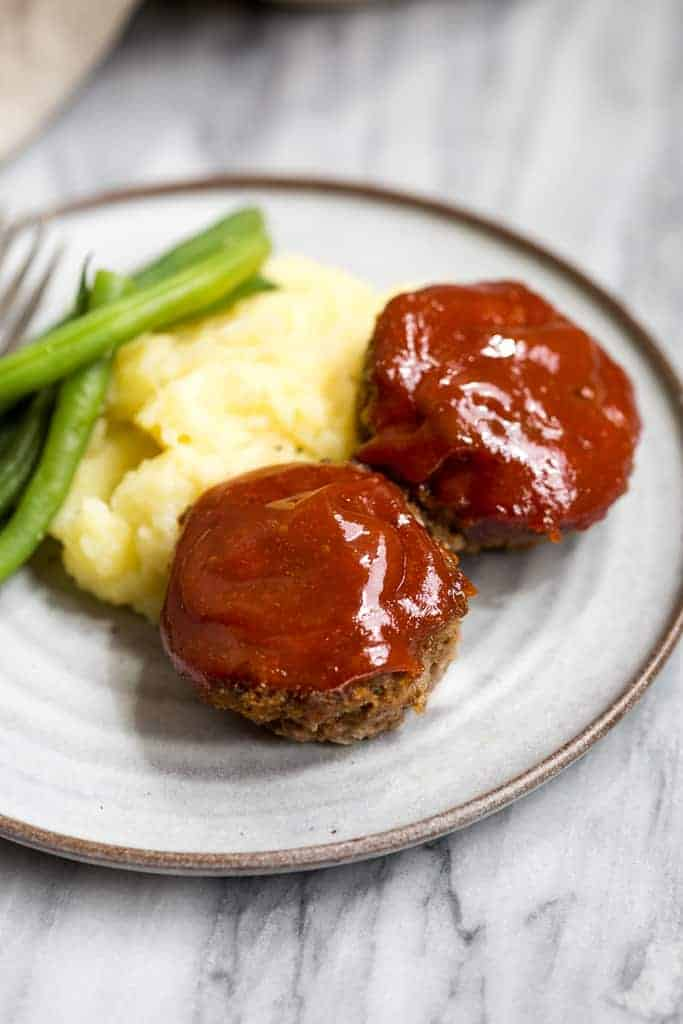 Two mini meatloaf muffins with meatloaf sauce on them on a plate with mashed potatoes and green beans.