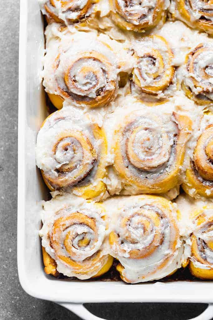 Close up photo of a pan of pumpkin cinnamon rolls with cream cheese frosting.