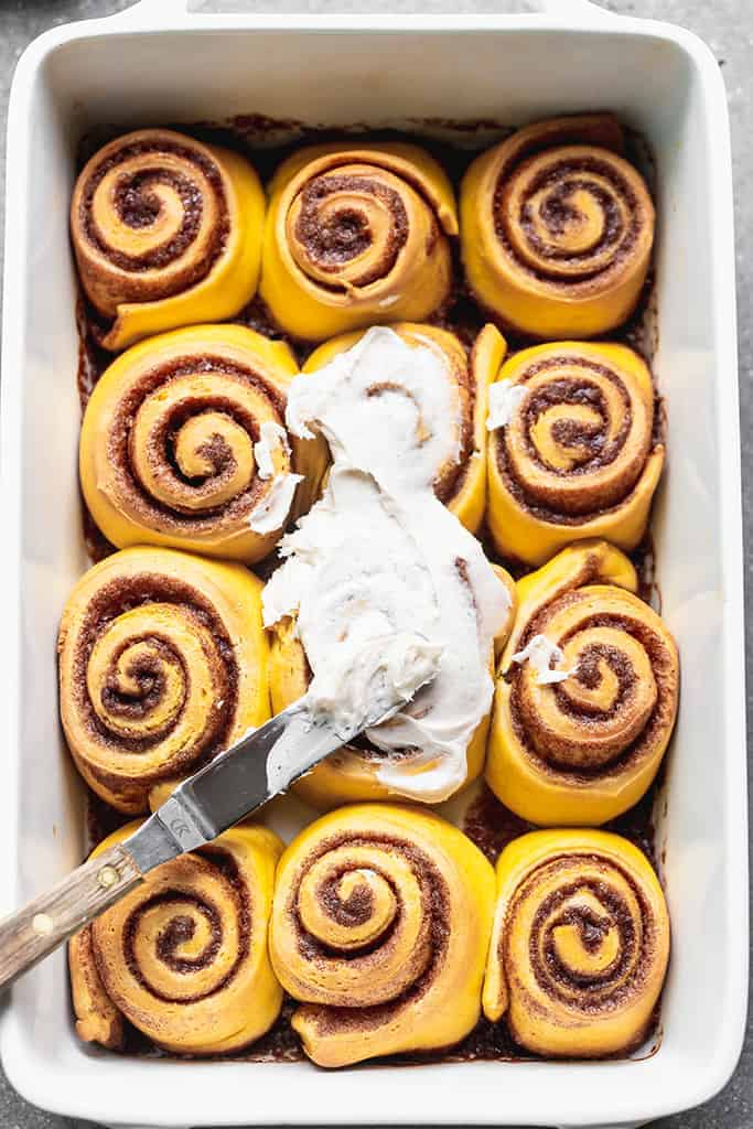 An off-set spatula spreading cream cheese frosting over pumpkin cinnamon rolls in a white pan..