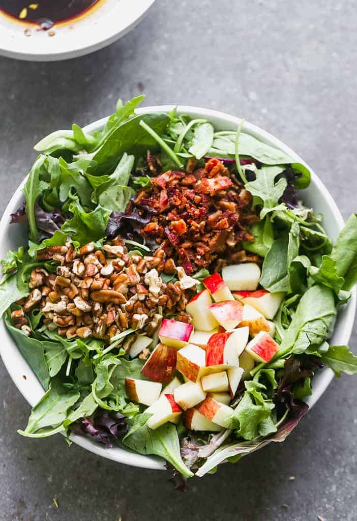 A green salad with three toppings laid in sections on top of the lettuce including chopped red apples, pecans and crumbled bacon.