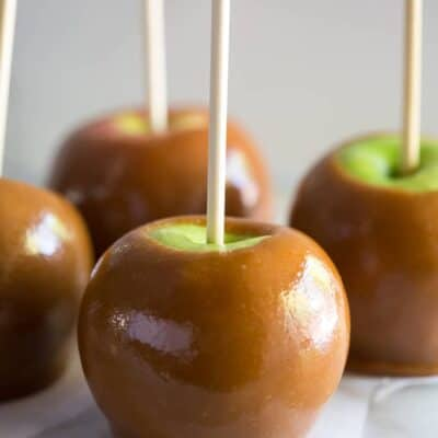 Four homemade caramel apples with a stick in them, on parchment paper on a white board.