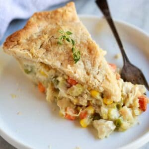 A slice of chicken pot pie with homemade crust and filling with vegetables and chicken, served on a white plate with a fork.