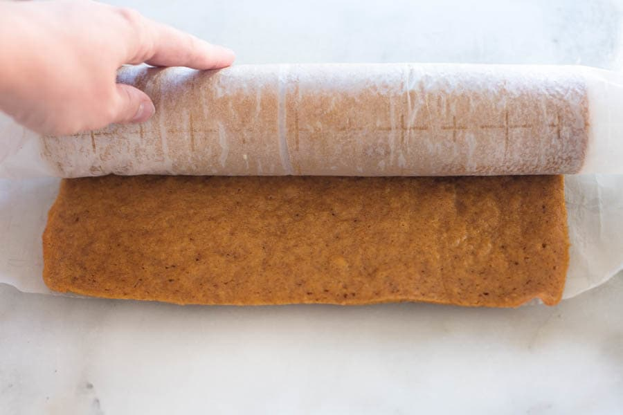 A cooked pumpkin roll, laying horizontally, and being rolled in parchment paper.