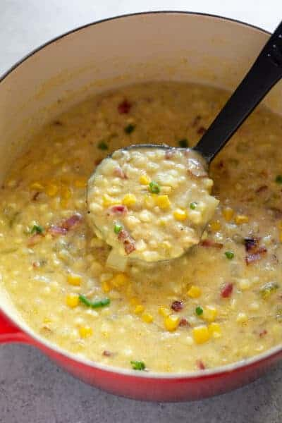 A soup pot full of corn chowder with a ladle spooning some out.