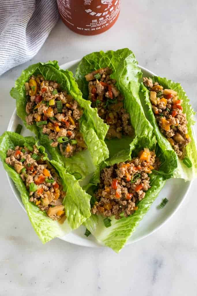 Overhead photo of a plate with romaine lettuce leaves filled with ground chicken and veggies filling for lettuce wraps.