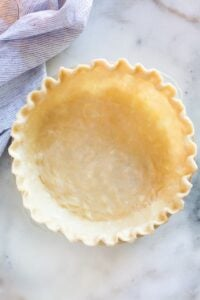 Pie crust with a crimped edge in a pie dish ready to be baked.
