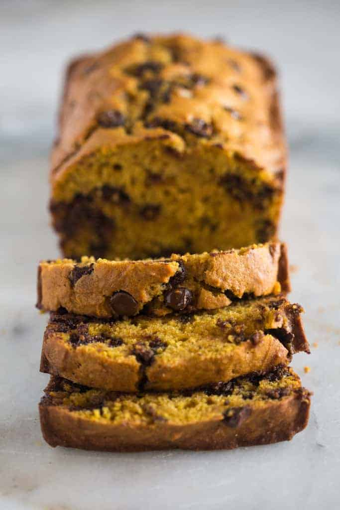 A loaf of pumpkin bread with chocolate chips with a few slices cut in it.