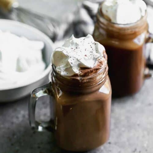 A mug of hot cocoa with fresh whipped cream on top, and another mug and bowl of whipped cream in the background.