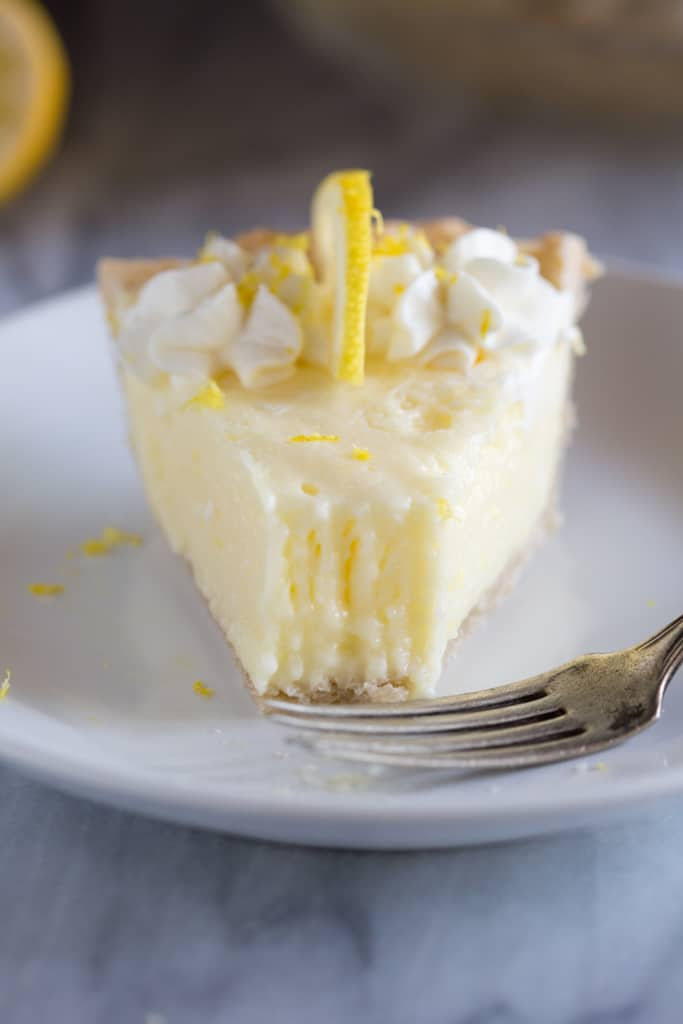 A slice of lemon pie on a plate with a fork and a bite taken out of the pie.