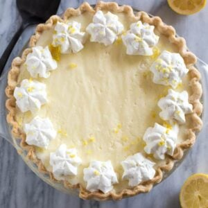 Overhead photo of a lemon chiffon pie with piped whipped cream and lemon zest.