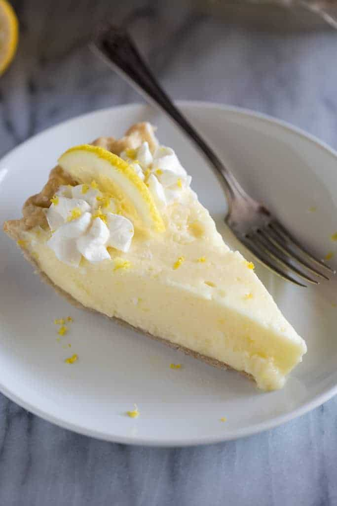 A piece of lemon pie with whipped cream and a slice of lemon on top, served on a white plate with a fork.
