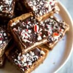 Peppermint Brownie squares with chocolate frosting and crushed candy canes on a white plate.