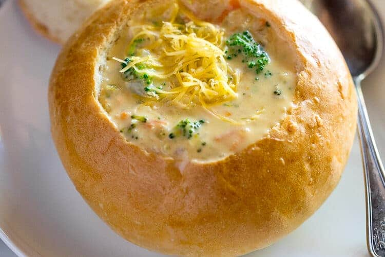 A homemade bread bowl on a white plate with the center cut out, resting on the edge of the plate, broccoli cheese soup in the bread bowl and a spoon on the side.