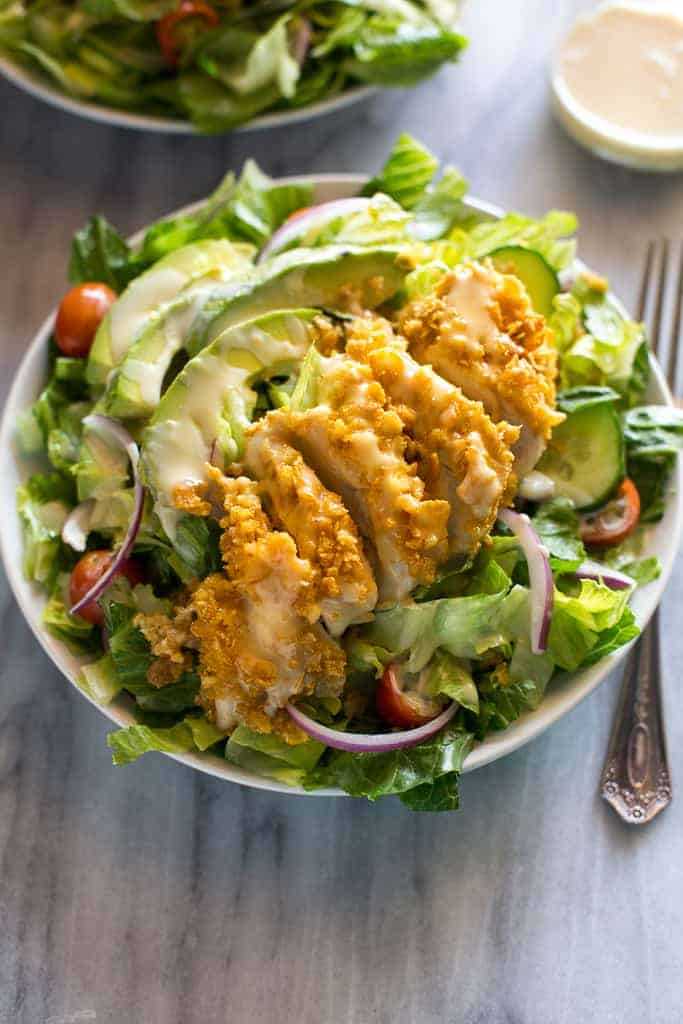 A green salad with cornflake crusted chicken, avocado and honey mustard dressing.