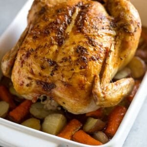 A roasted chicken on a bed of vegetables in a white 9 by 13 inch baking dish.