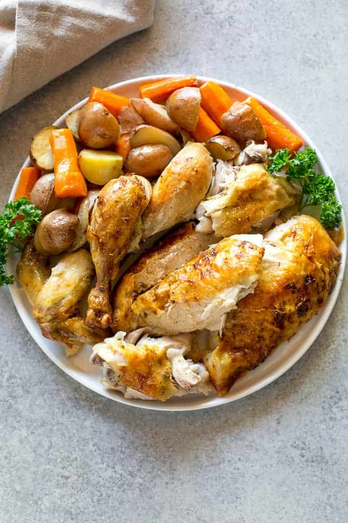 Overhead photo of a white plate with the carved meat from a whole chicken, cooked carrots, potatoes and onion.