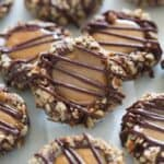 Turtle Thumbprint cookies on a baking sheet. | tastesbetterfromscratch.com