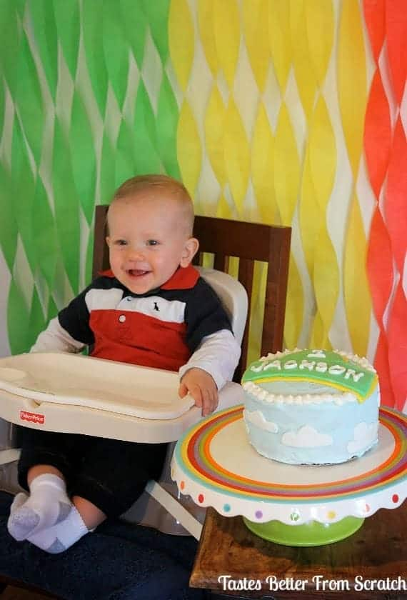 a one year old in a high chair next to his birthday cake.