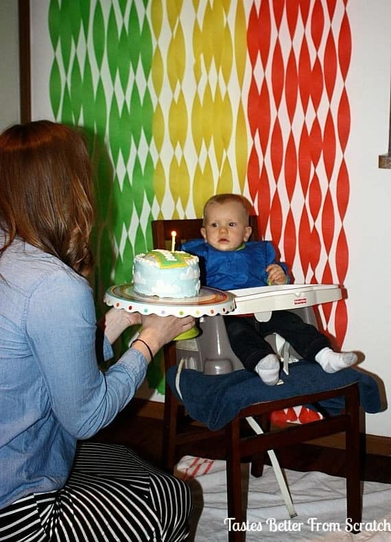 A mom presenting her one year old with his first cake.
