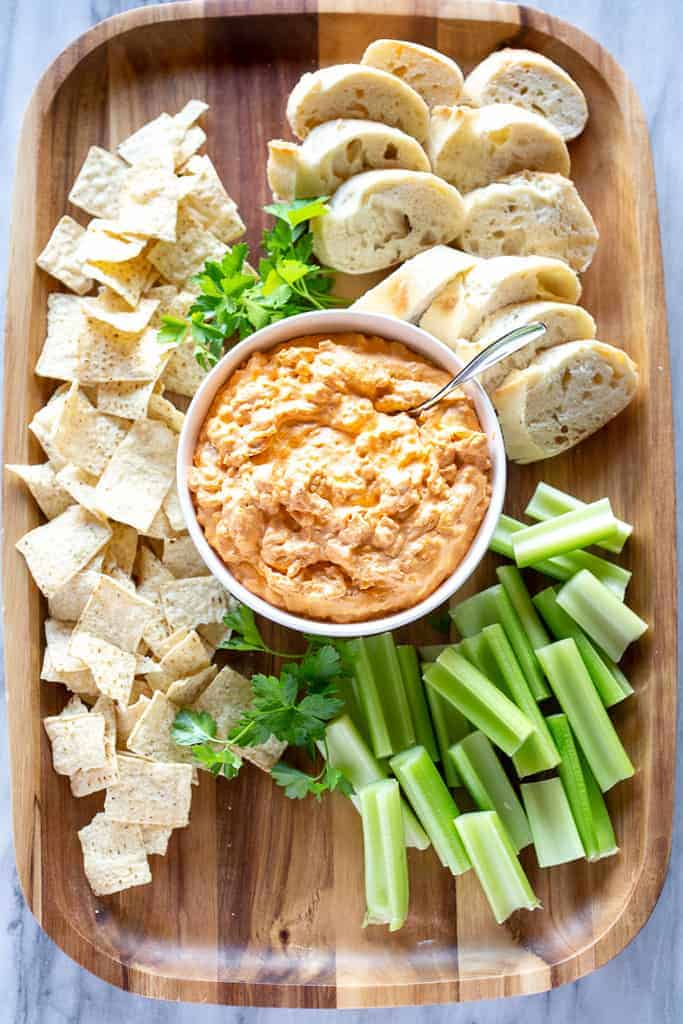 Buffalo Chicken Dip on a wood serving board with celery, chips and bread slices.