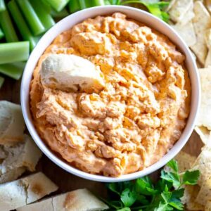 A bowl of buffalo chicken dip with bread slices, celery and chips around it.