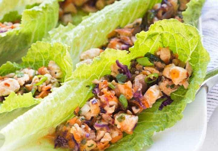 Thai Chicken Lettuce Wraps lined along a white plate.
