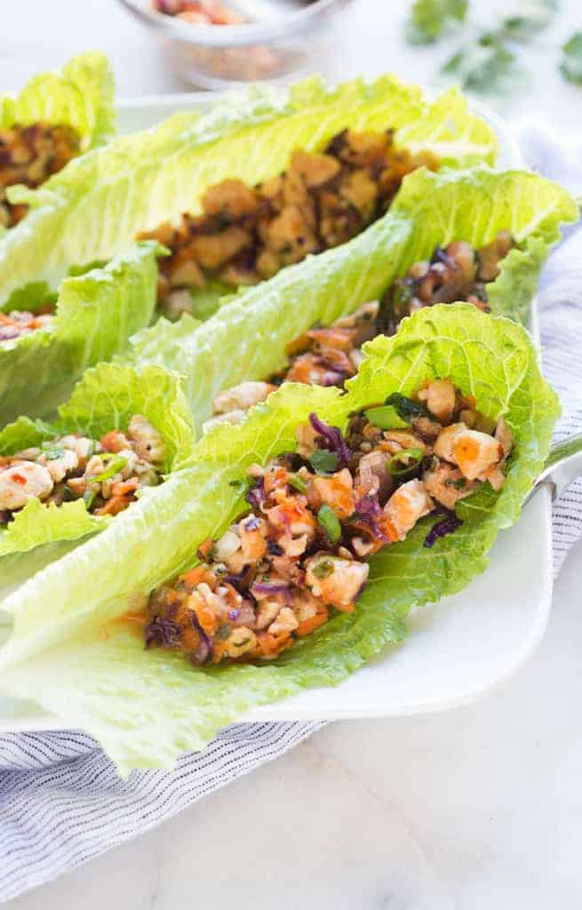 Thai Chicken Lettuce Wraps in romaine leaves on a plate.
