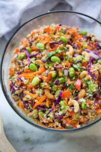 Quinoa tossed with a medley of fresh, crunchy veggies and drizzled with a delicious peanut sauce. Everyone always loves this fun and delicious and easy quinoa salad. | tastesbetterfromscratch.com