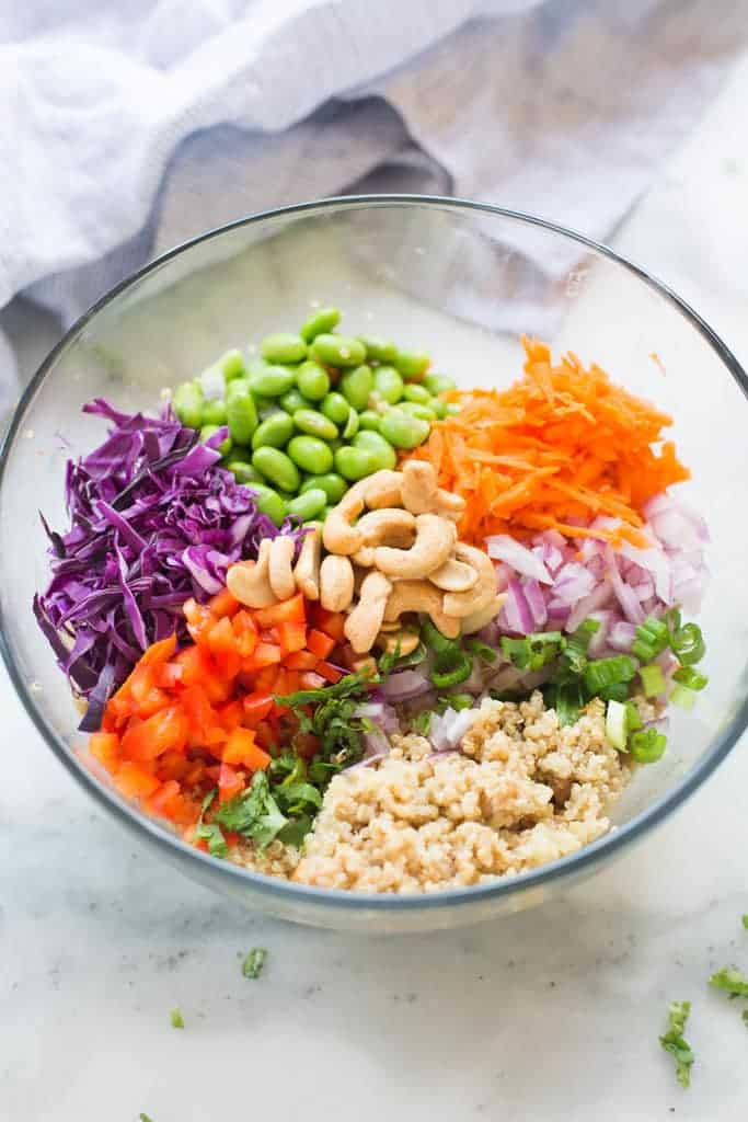 A bowl filled with edamame, cabbage, bell pepper, red onion, carrots, and quinoa.