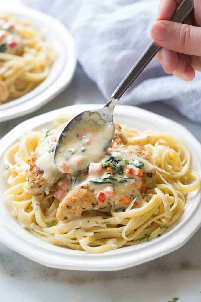 A big spoonful of tuscan garlic sauce over crispy, tender and juicy chicken, served over fettuccine noodles. Tuscan Garlic Chicken is one of my family's favorites! | tastesbetterfromscratch.com