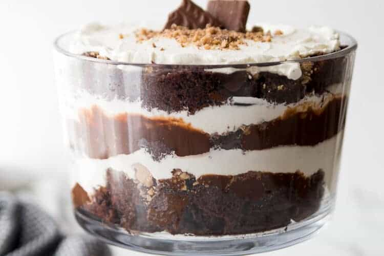 Chocolate trifle made with chocolate cake, whipped cream, chocolate pudding and heath candy, with a dish towel and crushed heath on the side.