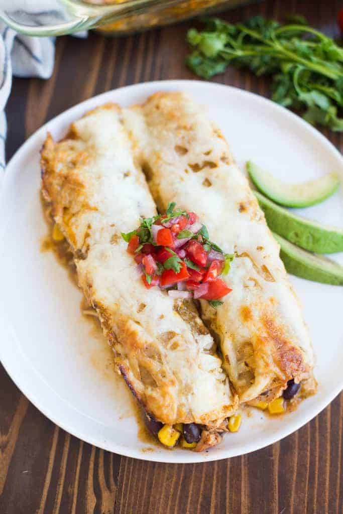 Two Chicken Enchiladas on a circular plate with avocado and salsa.