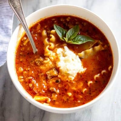 Lasagna Soup with a scoop of ricotta cheese on top and a spoon in the bowl.