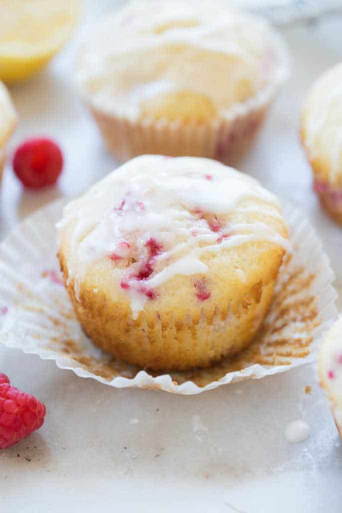 One Raspberry Lemon Muffin on a muffin wrapper that's been peeled away from it. |