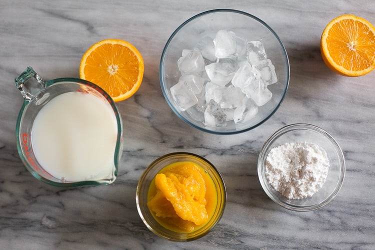 Overhead photo of the ingredients needed to make orange julius including orange juice concentrate, a liquid measuring cup with milk and water in it, a bowl of ice and a small bowl with powdered sugar.