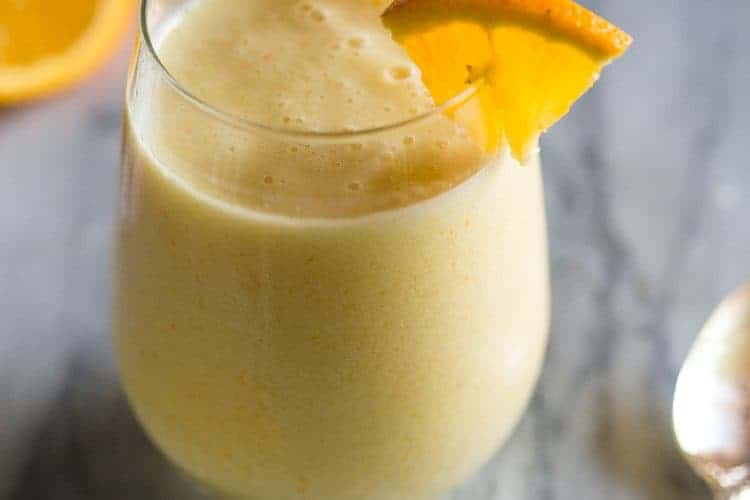A clear glass of orange julius with a wedge of an orange on the rim and a spoon and sliced oranges in the background.