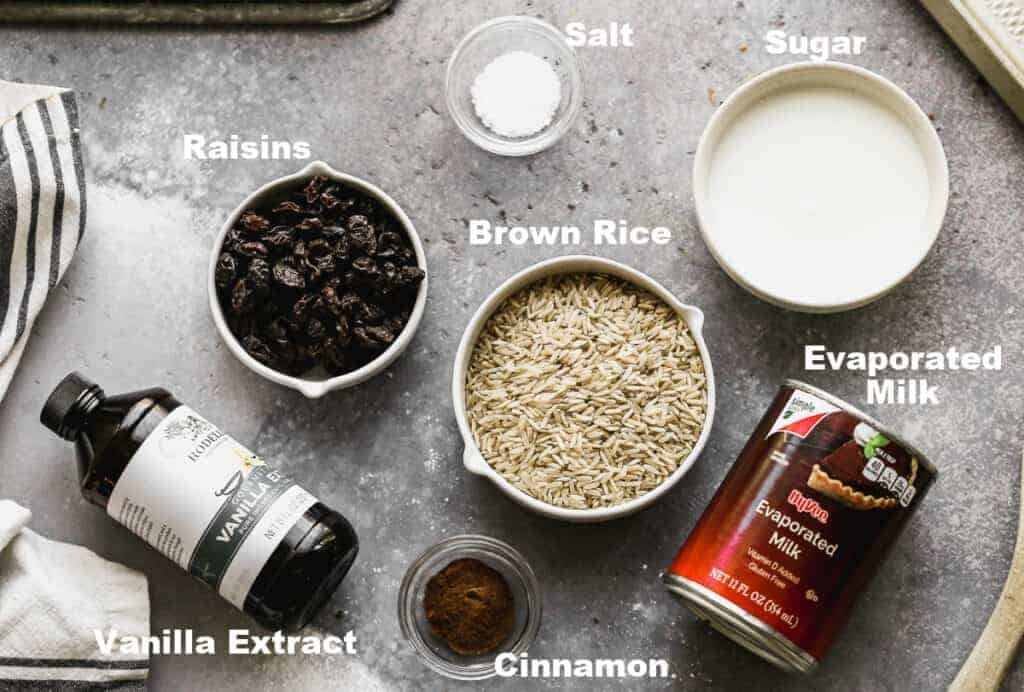 The ingredients needed to make Brown Rice Pudding, including uncooked rice, sugar, salt, evaporated milk, vanilla, cinnamon and raisins.