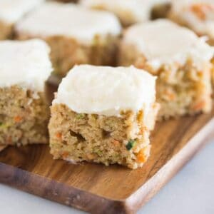 Carrot and zucchini bars with lemon cream cheese frosting on a wood cutting board.