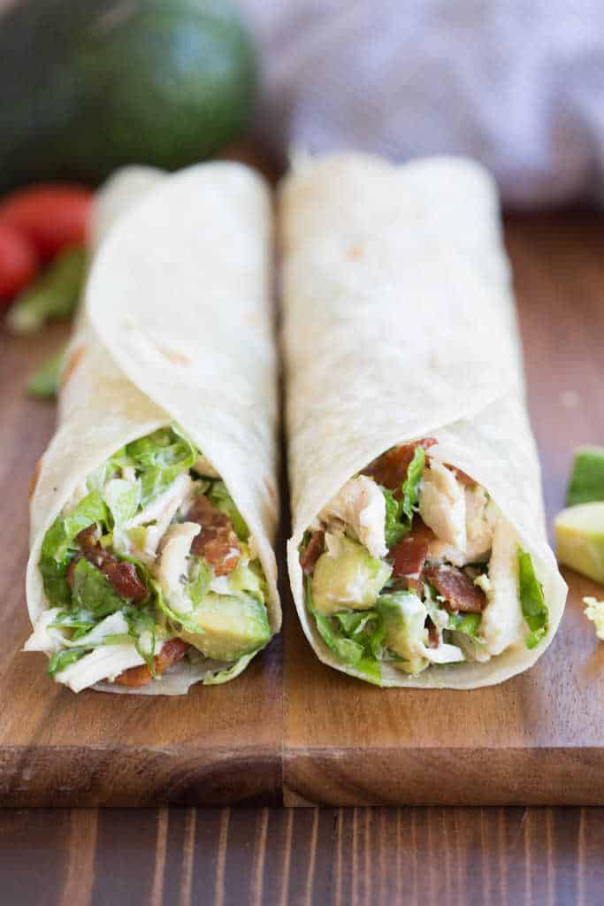 Two Chicken Bacon Avocado Wraps laying side by side on a wooden board.