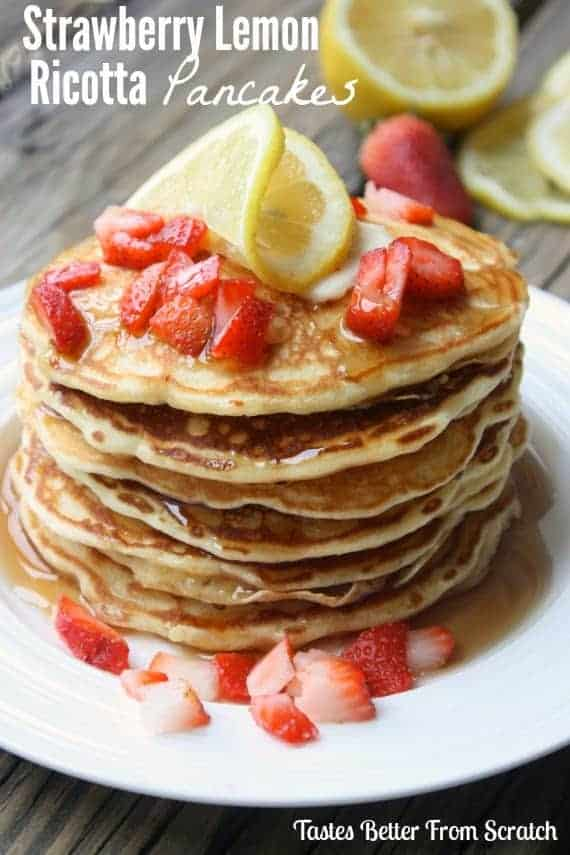 Strawberry lemon ricotta pancakes stacked on a white plate with strawberries.