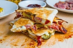 Ham, bacon, pineapple quesadillas stacked on a cutting board.