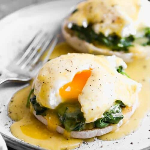 A plate with eggs florentine on it (english muffin topped with spinach, poached egg and hollandaise sauce).