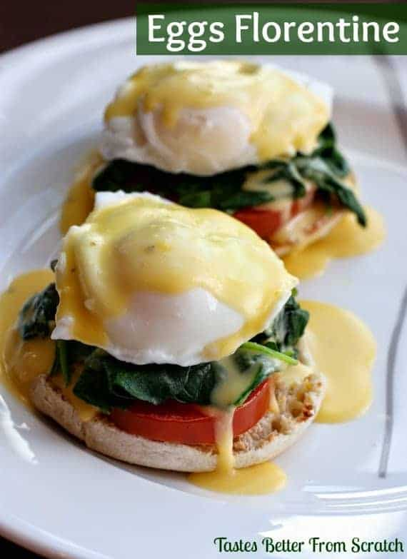 Two eggs florentine on a white plate with tomato, spinach, a poached egg, and homemade hollandaise sauce.