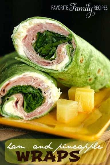A ham and pineapple wrap cut in half on a plate.