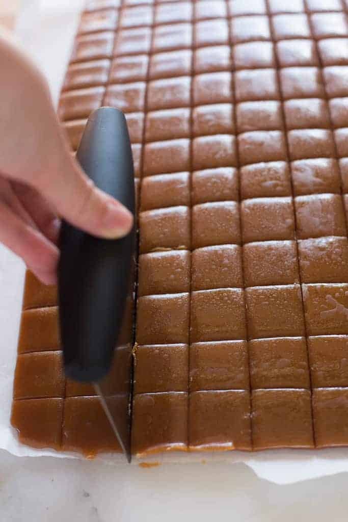A hand using a tool to cut caramels into small squares.