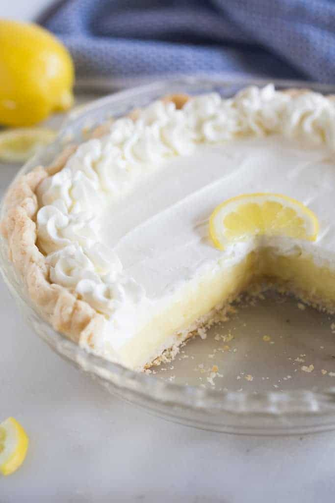 Lemon sour cream pie with a piece removed.